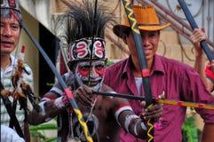 JAKARTA, INDONÉSIA 7 DE AGOSTO DE 2015: nativo a turistas de Irian Jaya que mostra como usar a curva tradicional com a seta para fotografia de stock royalty free
