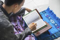 Devout male muslim reading Quran at home. JAKARTA - Indonesia. April 18, 2018: Devout male muslim reading Quran on the wooden stand during ramadan time at home royalty free stock images