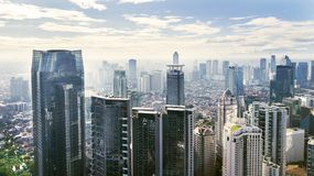 Jakarta cityscape with modern office buildings and apartments under blue sky. JAKARTA - Indonesia. March 12, 2018: Jakarta cityscape with modern office buildings Royalty Free Stock Image