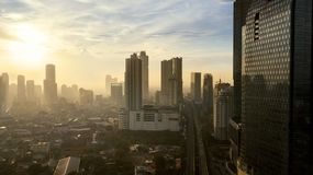 High buildings and housing at sunset time. JAKARTA - Indonesia. May 21, 2018: Aerial cityscape view of Jakarta with high buildings and residential houses at Stock Image