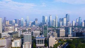 Jakarta downtown under blue sky. JAKARTA - Indonesia. May 21, 2018: Aerial view of Jakarta downtown with skyscrapers and residential house under blue sky Stock Photos