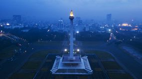 National Monument at night time. JAKARTA - Indonesia. May 21, 2018: Aerial view of National Monument with Istiqlal mosque and skyscrapers at night time Stock Image