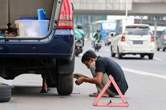 The man change the tires by himself beside the road at the center of Jakarta. Jakarta, Indonesia May 6, 2019: The man change the tires by himself beside the road royalty free stock image