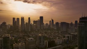 Aerial view of skyscrapers and residential houses in Jakarta city during sunset royalty free stock photography