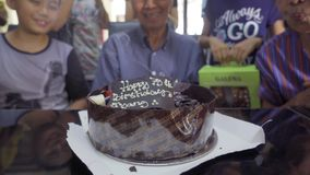 Grandfather blows out birthday cake candles stock video footage