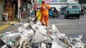 Sweeper cleaning road from newspaper garbage Royalty Free Stock Photography