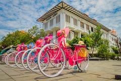 JAKARTA INDONESIEN - MAJ 06, 2017: Raden av rosa färger cyklar med att matcha hattar parkerade framme av Jakarta historiemuseum p Arkivfoton