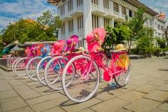 JAKARTA INDONESIEN - MAJ 06, 2017: Raden av rosa färger cyklar parkerat framme av Jakarta historiemuseum på ett härligt soligt royaltyfri fotografi