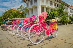 JAKARTA INDONESIEN - MAJ 06, 2017: Raden av rosa färger cyklar parkerat framme av Jakarta historiemuseum på ett härligt soligt arkivbilder