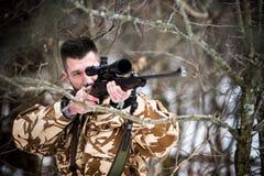 Jakt armé, militärt begrepp - prickskyttinnehavgevär och sikta på målet i skogen under operation Arkivfoton