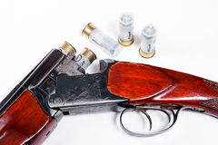Jakthagelgevär och ammunitionar på vit bakgrund Arkivfoto