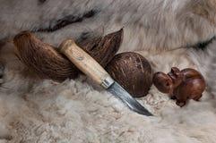 Jaktkniv med ett trähandtag, på huden med en kokosnöt arkivfoton