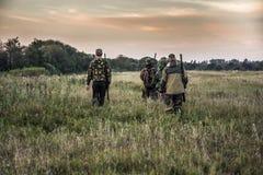 Jaktplats med jägare som går till och med lantligt fält under jaktsäsong i mulen dag under solnedgång med lynnig himmel Arkivbild