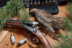 Jakttrofé - rapphöna, gevär, kassettbälte, ammunition, på träbräden Royaltyfri Fotografi