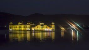 Jal Mahal At Jaipur entre a água do lago - opinião da noite fotos de stock royalty free