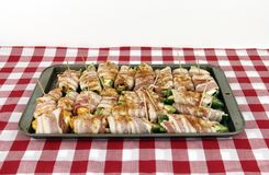 Jalapeno Peppers wrapped in bacon. On a baking sheet royalty free stock image