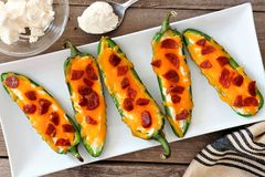 Jalapeno poppers with cheese and pepperoni on a white plate. Group of jalapeno poppers with cheese and pepperoni on a white serving plate, overhead scene Royalty Free Stock Photos