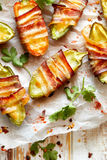Jalapeno poppers wrapped in bacon stuffed with cheese seasoned with herbs and spices, delicious starter. Jalapeno poppers wrapped in bacon stuffed with cheese stock images