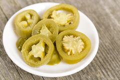 Jalapenos. Bowl of pickled sliced green jalapeno peppers on a wooden background Stock Photos