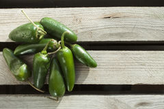 Jalapenos. A lot of green jalapenos, on a wooden background Royalty Free Stock Photos