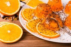 Jalea anaranjada con microprocesadores de chocolate, una cuchara y las rebanadas de naranjas Imagen de archivo
