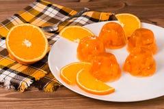 Jalea anaranjada y rebanadas anaranjadas en una placa Fotos de archivo