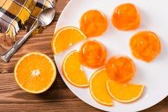 Jalea y rebanadas anaranjadas de naranja en una placa en una tabla de madera Imagenes de archivo