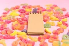 Jaleas azucaradas y libreta en blanco en fondo rosado Lugar para su texto fotografía de archivo