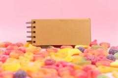 Jaleas azucaradas y libreta en blanco en fondo rosado Lugar para su texto imágenes de archivo libres de regalías