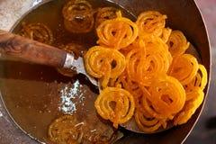 Jalebi délicieux faisant frire dans le bac à huile Photographie stock libre de droits