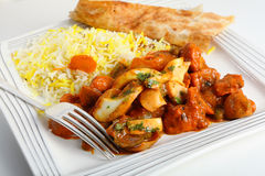 Jalfrezi fork and plate. Chicken jalfrezi curry on a plate with pilau rice and a piece of naan bread Stock Photos