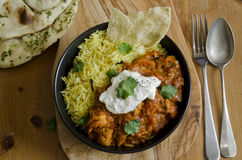 Jalfrezi with rice. Jalfrezi Indian chicken curry with pilau rice and pappadom topped with yogurt Stock Photos