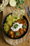 Jalfrezi with rice. Jalfrezi Indian chicken curry with pilau rice and pappadom topped with yogurt Royalty Free Stock Image