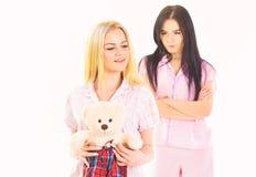 Jaloersheid en afgunstconcept De zusters in pyjama's kijkt vijandig, jaloers Meisjes in roze pyjama's, geïsoleerd wit royalty-vrije stock afbeelding