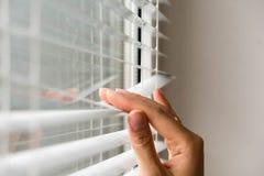 Jalousie de Windows femme jetant un coup d'oeil par des abat-jour de fenêtre Main masculine séparant des lamelles des abat-jour v Image stock