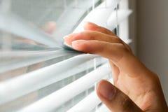 Jalousie de Windows femme jetant un coup d'oeil par des abat-jour de fenêtre Main masculine séparant des lamelles des abat-jour v Photographie stock libre de droits