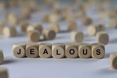Jaloux - cube avec des lettres, signe avec les cubes en bois Photographie stock libre de droits