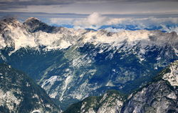 Jalovec, Mangart peaks and forested Trenta Valley, Julian Alps. Jalovec, Mangart peaks, Mojstrovke ridge, dark green pine forests of Trenta Valley, Julian Alps Stock Photo