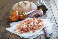 Jamón con pan, el tomate, el ajo y el aceite de oliva fotografía de archivo libre de regalías