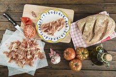 Jamón con pan, el tomate, el ajo y el aceite de oliva foto de archivo libre de regalías
