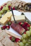 Jamón, microprocesadores y galletas, aceitunas, uvas, fresas y queso Foto de archivo
