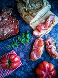 Jamón, tomate, pan e hierbas en la composición en fondo oscuro foto de archivo