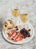 Jamón, uvas, pan del ciabatta y dos vidrios con el vino blanco Imagen de archivo