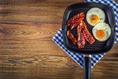 Jamón y huevo Tocino y huevo Huevo salado y asperjado con pimienta negra Tocino asado a la parrilla, dos huevos en una cacerola d Imagen de archivo
