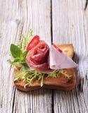 Jamón y salami en tostada Imagenes de archivo