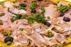Jamón y salami fino cortados con verdes Fotos de archivo libres de regalías