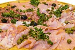 Jamón y salami fino cortados con verdes Fotografía de archivo libre de regalías