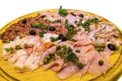 Jamón y salami fino cortados con verdes Imágenes de archivo libres de regalías