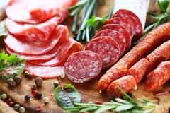 Jamón y salami italianos con las hierbas Fotos de archivo libres de regalías
