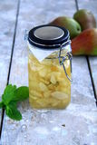 Jam. And pear standing on a wooden table Royalty Free Stock Photography